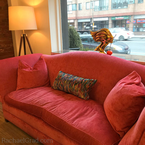 abstract multicolor pillow on pink couch by artist rachael grad