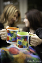 Load image into Gallery viewer, Mugs with orange and green art in hands cheers by Toronto Artist Rachael Grad