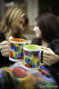 Mugs with orange and green art in hands cheers by Toronto Artist Rachael Grad
