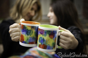 Mugs with orange and green art in hands cheers closeup by Toronto Artist Rachael Grad