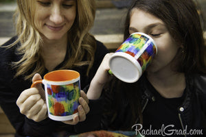 Mugs with orange and green art in Mom and Daughter hands and drinking by Toronto Artist Rachael Grad