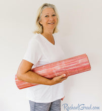 Load image into Gallery viewer, yoga mat by Canadian artist Rachael Grad for pilates on demand rolled up held by woman