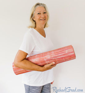 yoga mat by Canadian artist Rachael Grad for pilates on demand rolled up held by woman