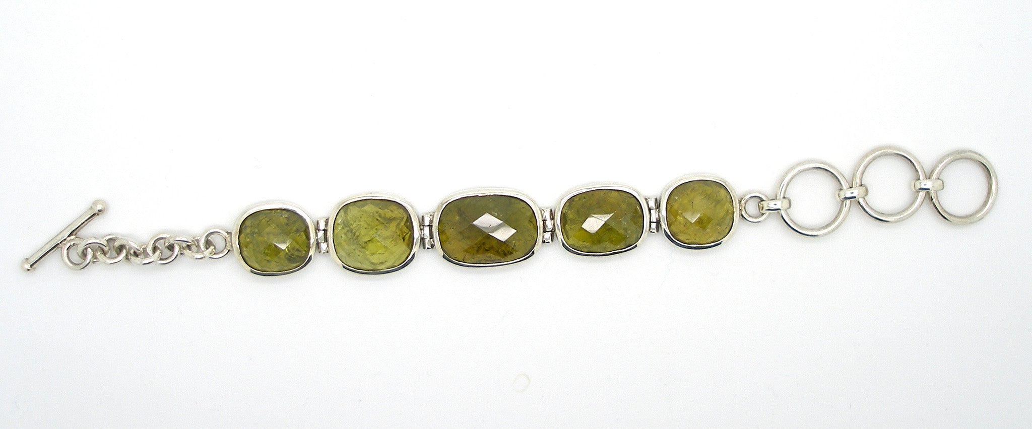 5 large faceted Grossular Garnets, Besel set, hinged together to make a very different Bracelet | These rare Garnets are Green, the name comes from the Latin for Gooseberry | Adjustable length up to 180 mm | Crystal Heart Melbourne since 1986