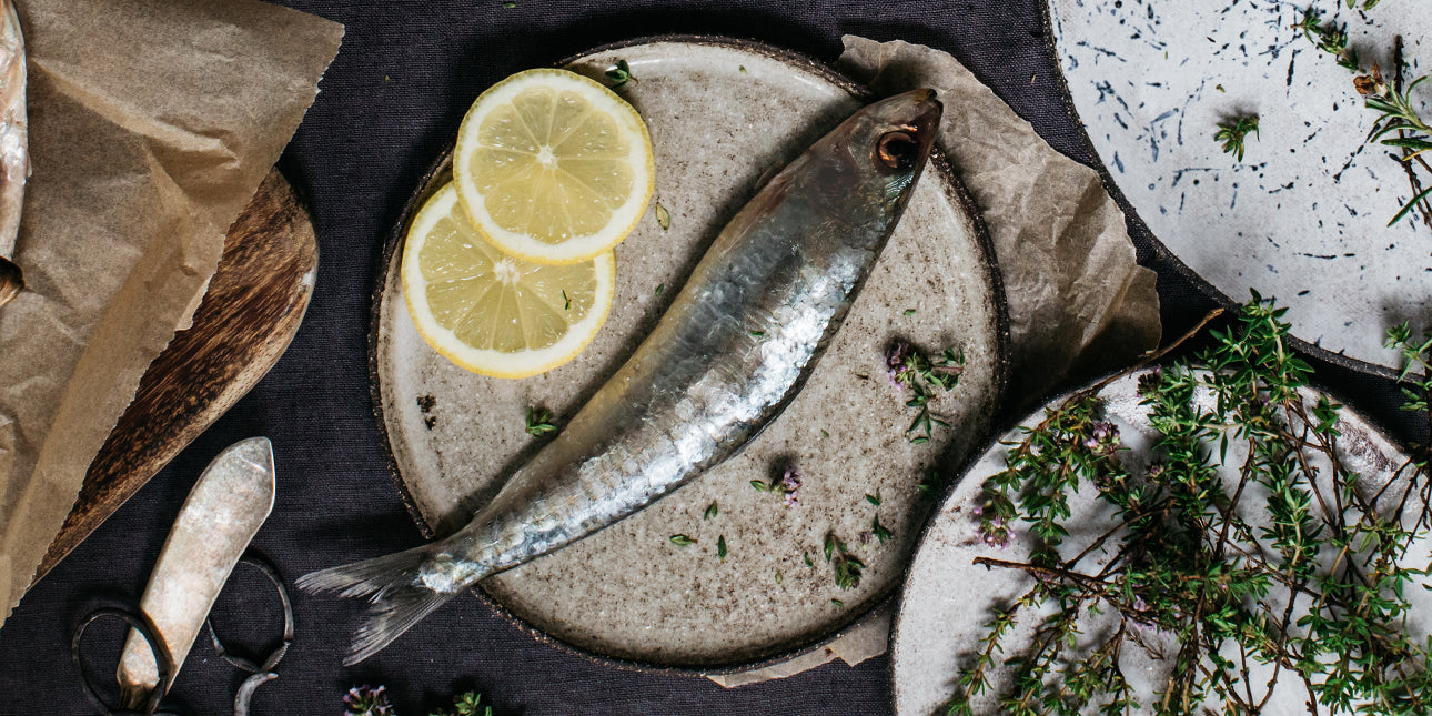 bare-biology-omega-3-a-fresh-sardine-on-a-plate-with-lemons