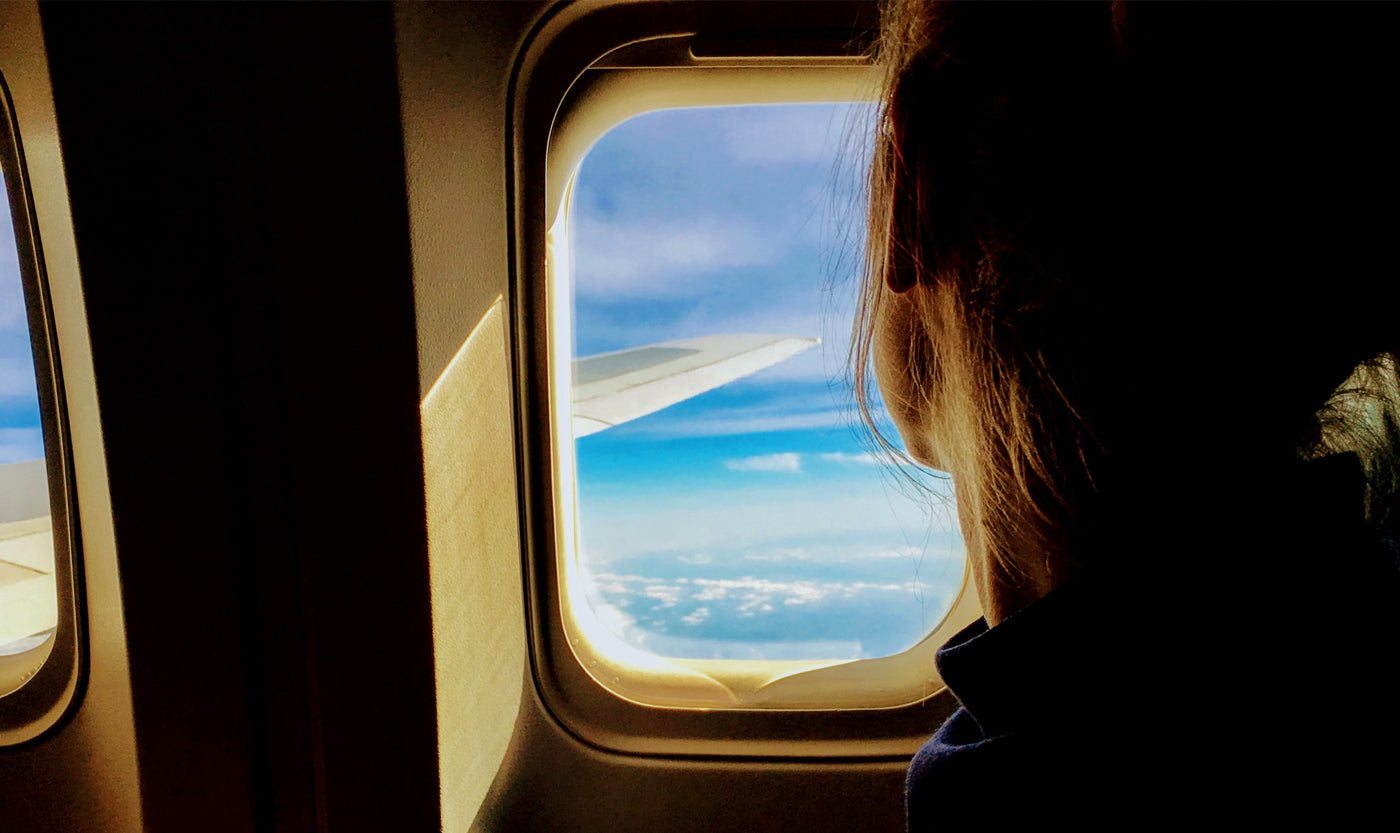 a-woman-looking-out-of-a-window-seat