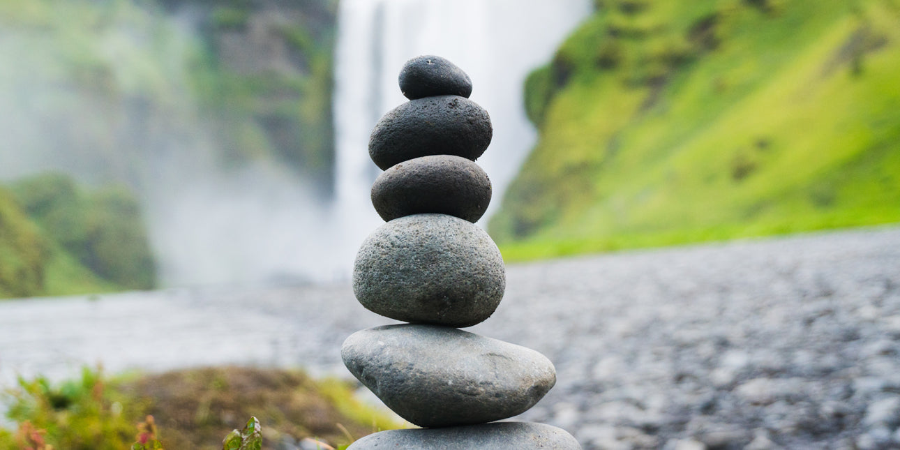 a stack of pebbles balancing on top of eachother next to a waterfall