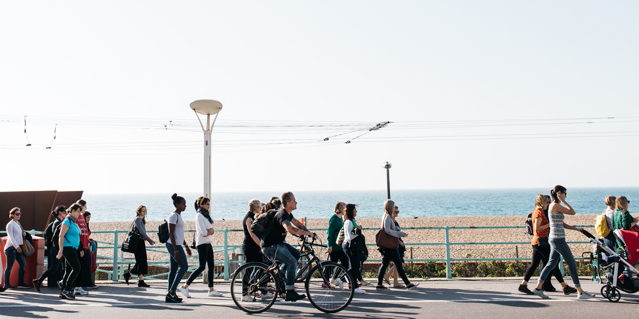 a-crowd-of-people-walking-along-brighton-seafront
