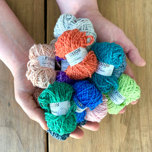 Eco-Bonbons in Nurturing Fibres Eco-Fusion, assorted colors, arranged on the palms of someone's hands