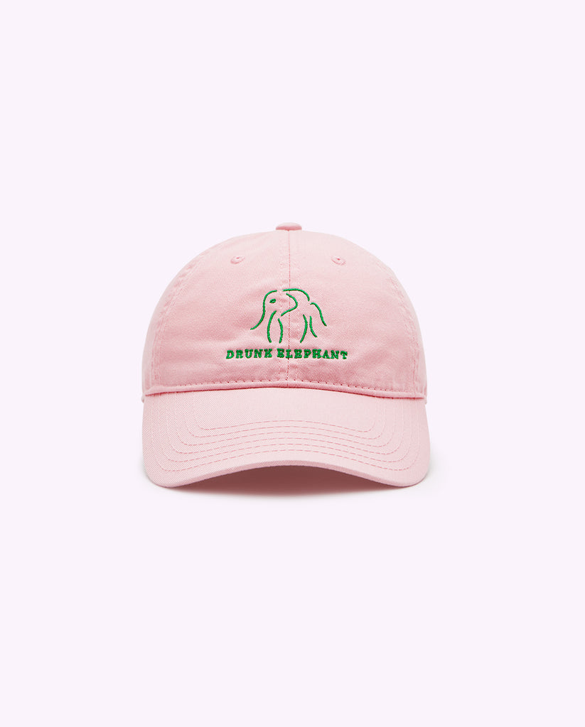 Pink Drunk Elephant baseball cap and green Drunk Elephant logo against a light pink background