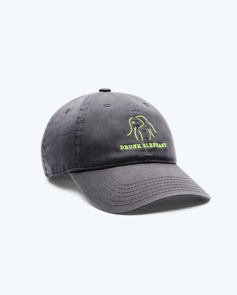 view of a charcoal Drunk Elephant baseball cap and bright green Drunk Elephant logo turned toward the right against a white background