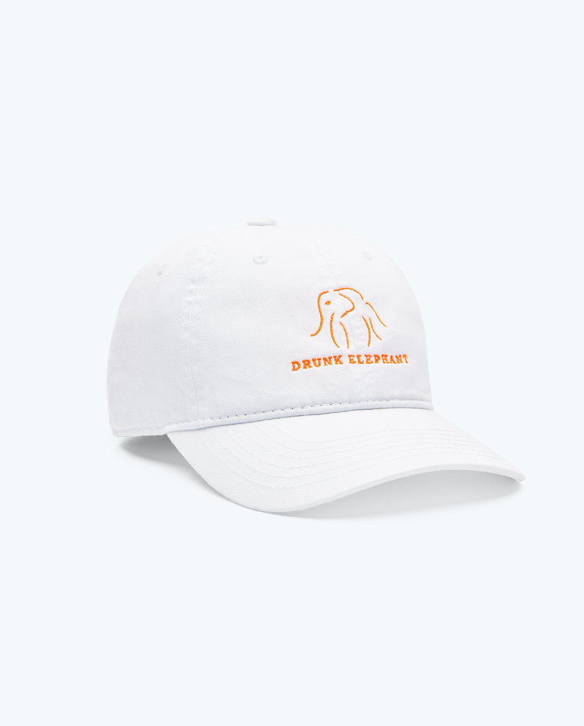 white Drunk Elephant baseball cap and orange Drunk Elephant logo against a white background turned toward the right