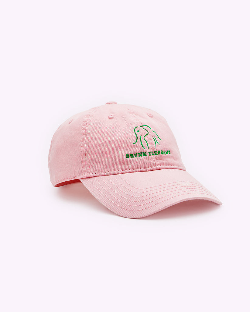 Pink Drunk Elephant baseball cap and green Drunk Elephant logo against a light pink background with the bill turned toward the right
