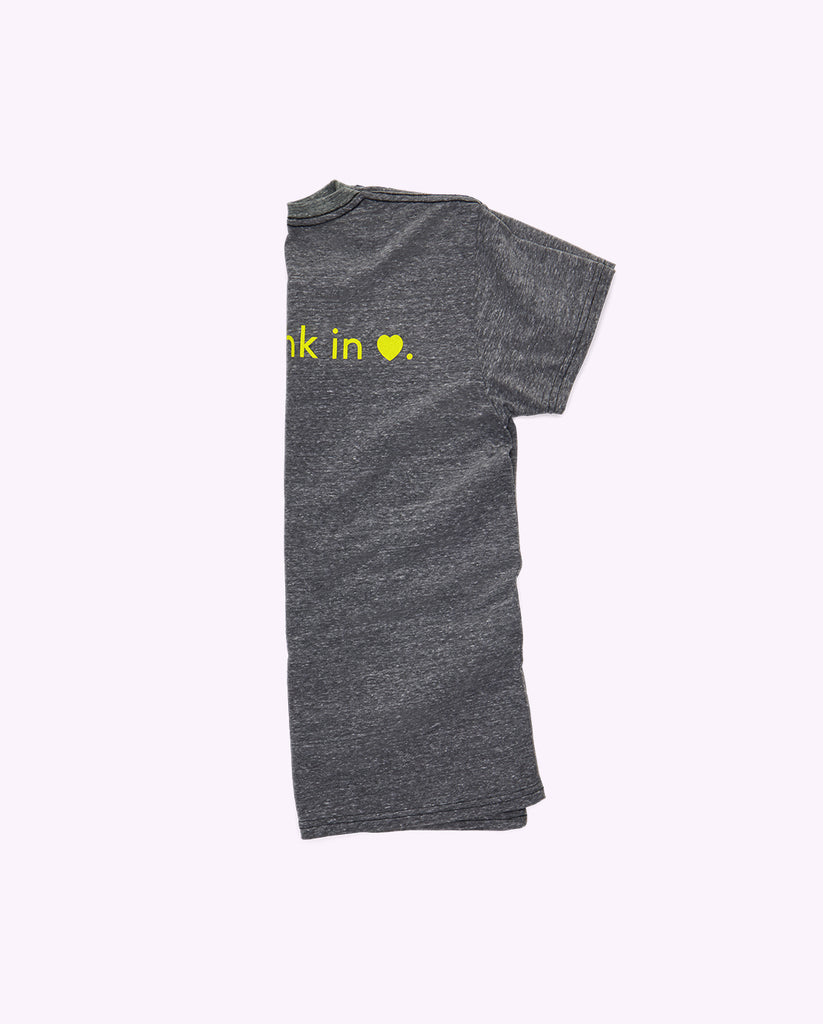 "heathered gray cotton crewneck t-shirt folded in half lengthwise showing the back of the shirt and the last half of the phrase ""i'm drunk in love"" showing where the word ""love"" is represented by a heart symbol"