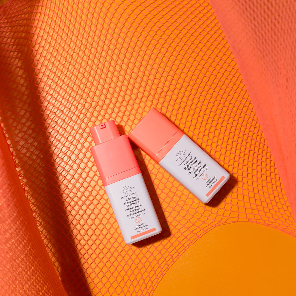 Two bottles of C-Tango Multivitamin Eye Cream laying flat against a textured orange background