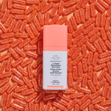 Decorative image of C-Tango Multivitamin Eye Cream laying against a background of orange vitamin capsules