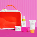 neon orange dopp kit displayed against a striped background with Marula Oil, TLC Framboos Glycolic Night Serum and Beste number 9 displayed next to it