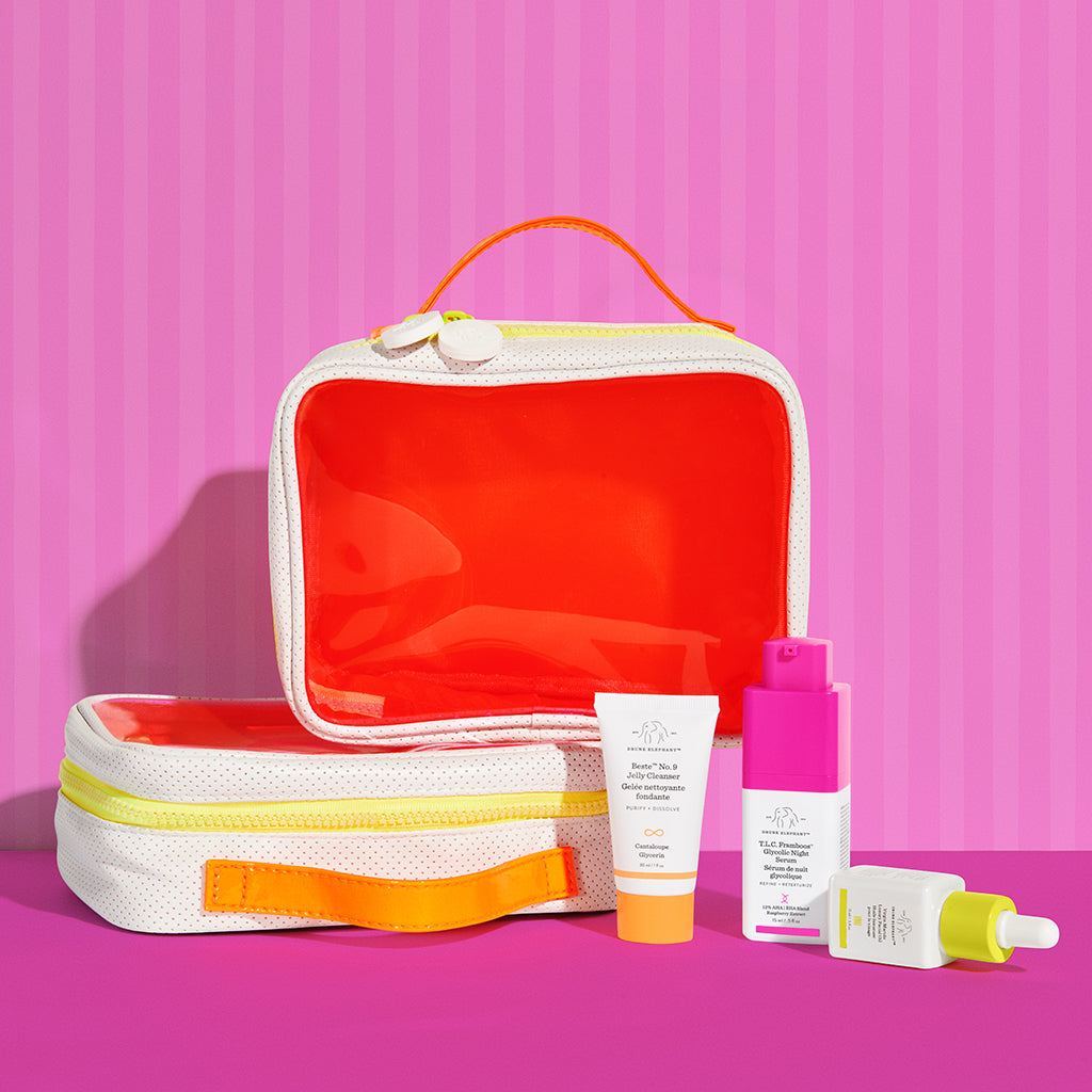two neon orange dopp kits stacked one on top of the other with Marula Oil, TLC Framboos Glycolic Night Serum and Beste number 9 displayed next to them