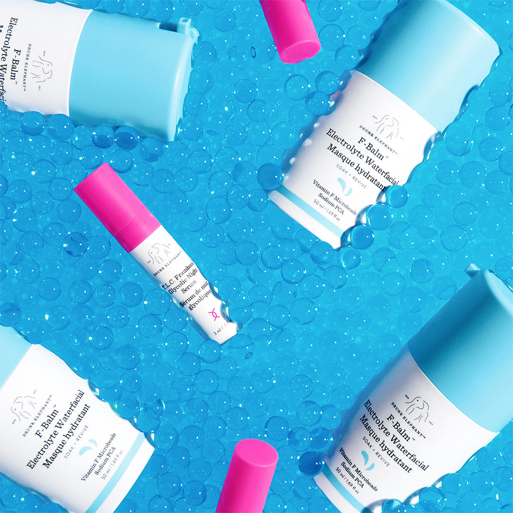 colorful image of four F-Balm Electrolyte Waterfacial pumps and three of the companion TLC Framboos Glycolic Night Serum deluxe samples laying on a blue background of glass beads that mimic water