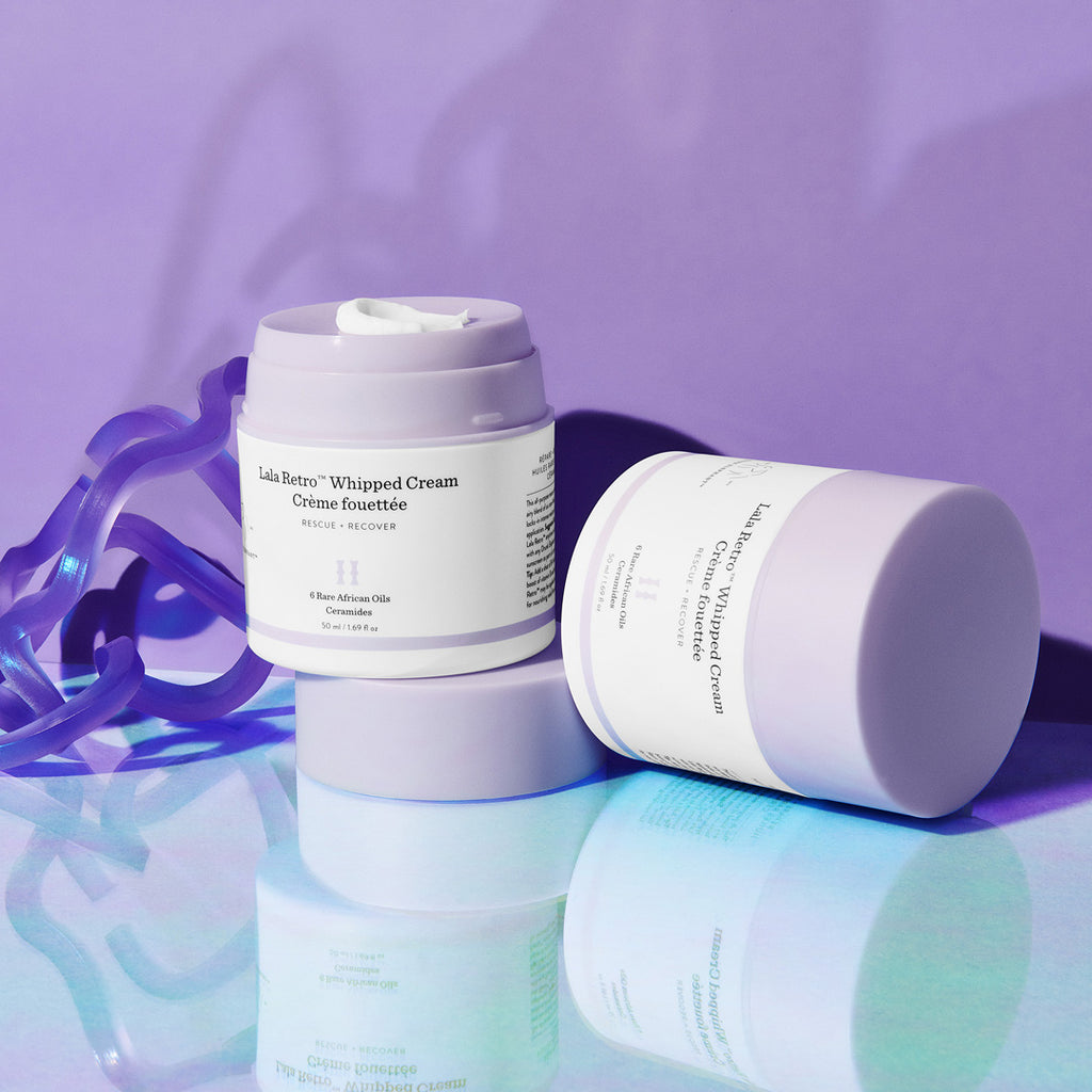A colorful image of two jars of Lala Retro Whipped Cream moisturizer with Ceramides. One jar is sitting on top of its cap and has product on top while the second jar is capped and laying on its side. The background is an iridescent table top and a purple wall.