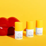 three Lippe lip balms lined up in front of glossy cartoon red lips against a bright yellow background