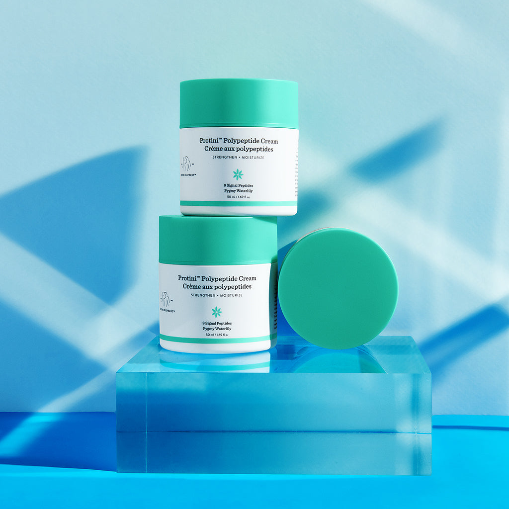three Drunk Elephant Protini Polypeptide Cream moisturizer pumps piled upon a clear acrylic block against a light blue background
