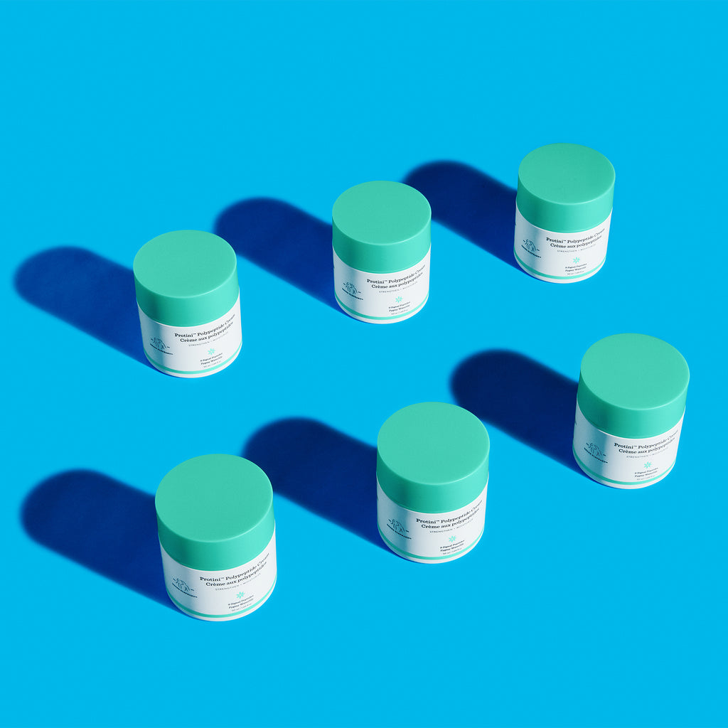 six Drunk Elephant Protini Polypeptide Cream moisturizer pumps lined up in two rows with shadows against a bright blue background