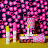 two Drunk Elephant Night Bright Duo canisters and one set of TLC Framboos Glycolic Night Serum and Marula Oil pumps to the left against a pink and black wall and bright yellow surface