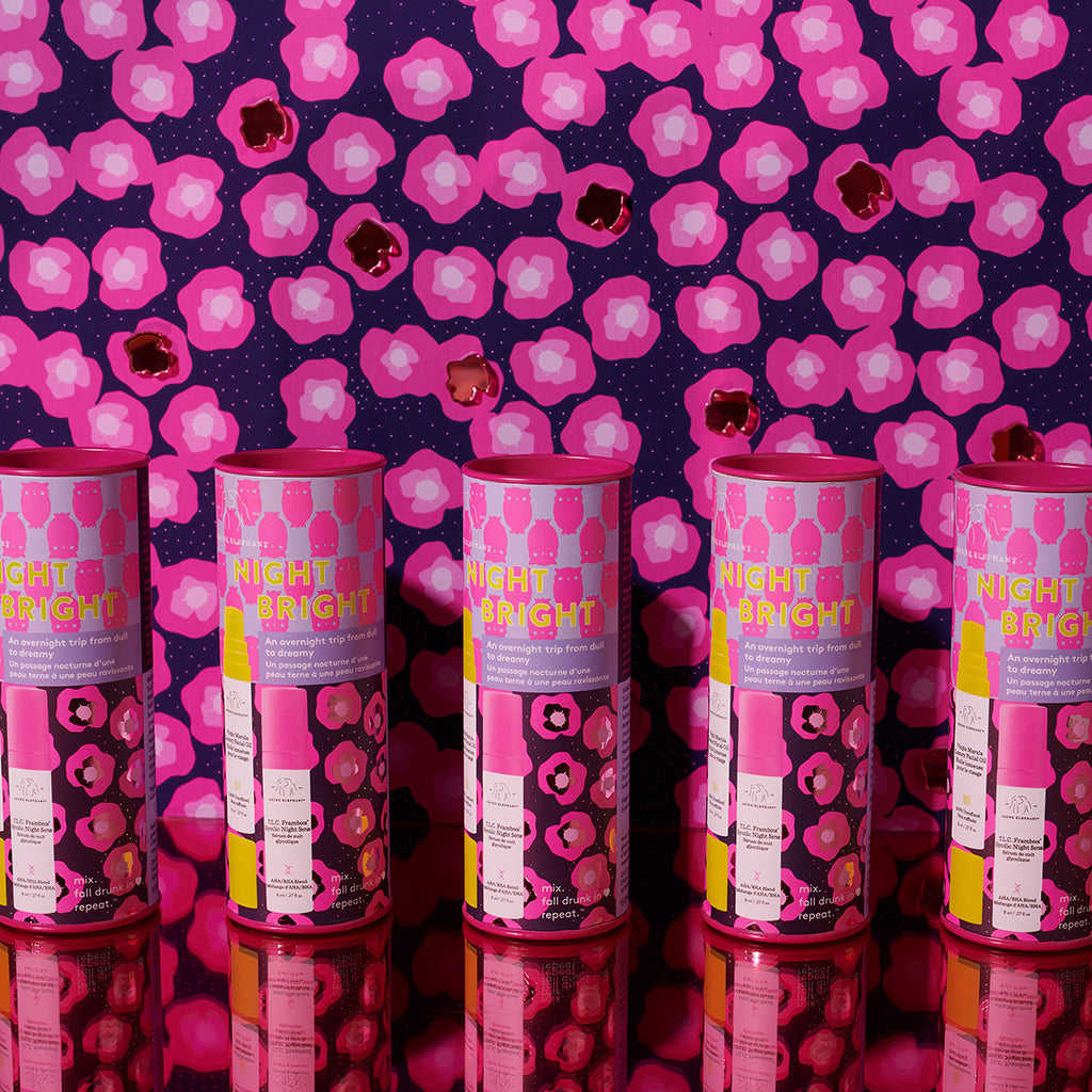five Drunk Elephant Night Bright Duo canisters lined up against a pink and black wall and bright yellow surface
