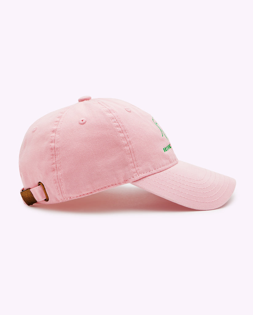 side view of a Pink Drunk Elephant baseball cap and green Drunk Elephant logo against a light pink background