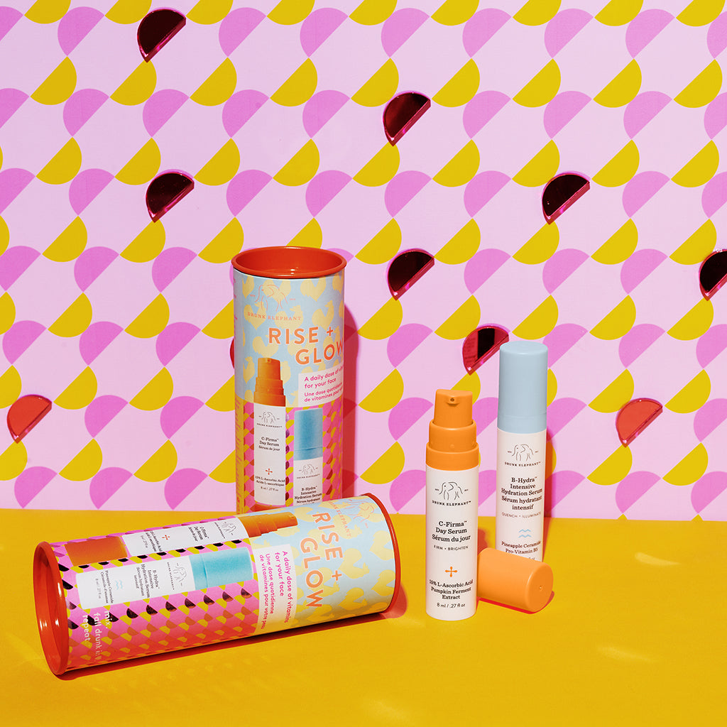 two canisters of Rise and Glow with one package on its side and one set of C-Firma and B-Hydra pumps against a pink, yellow and red patterned wall and yellow surface