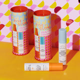 two canisters of Rise and Glow and one set of C-Firma and B-Hydra pumps against a pink, yellow and red patterned wall and yellow surface