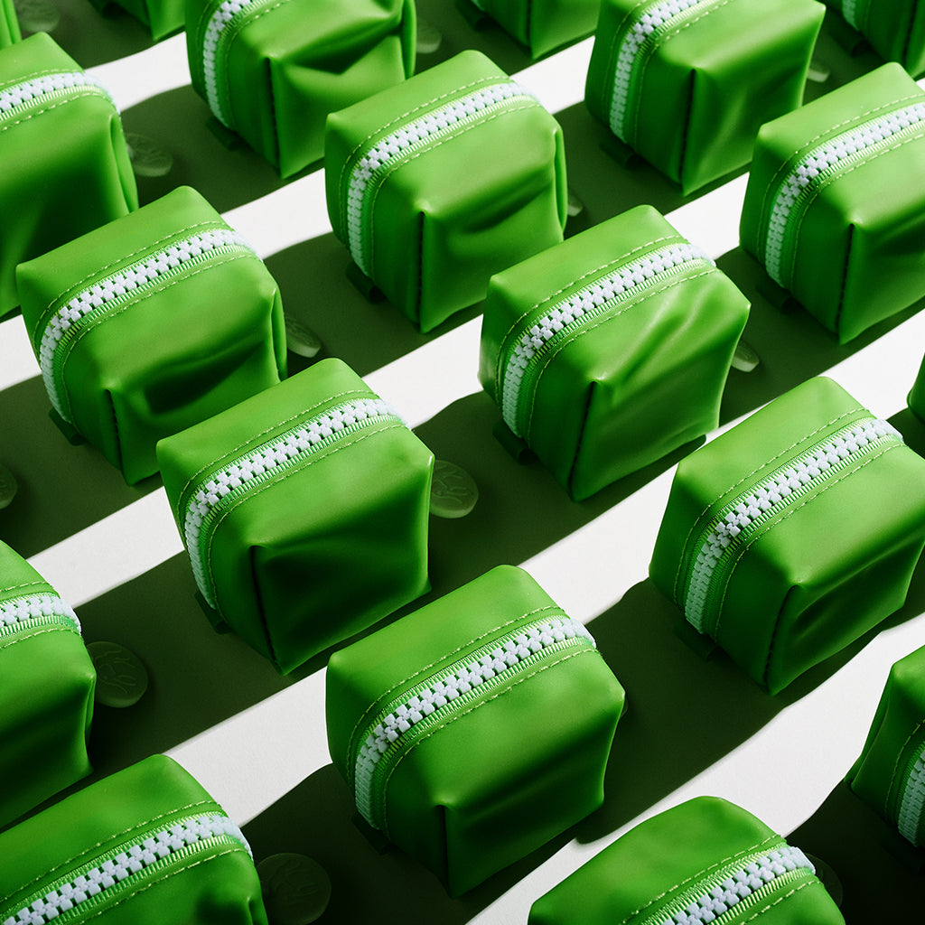 several green zippered travel cases lined up in rows with contrasting shadows