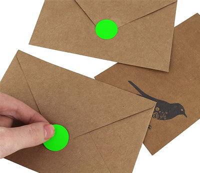 Green Sticker being placed on a kraft envelope