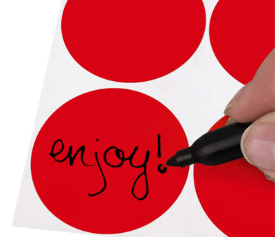 A Person's hand writing the word Enjoy on a Removable sticker with a felt tip marker