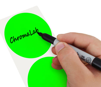 A Person's hand writing the word ChromaLabel on a sticker with a felt tip marker