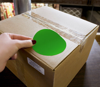 Woman's hand placing Green Sticker on a cardboard box