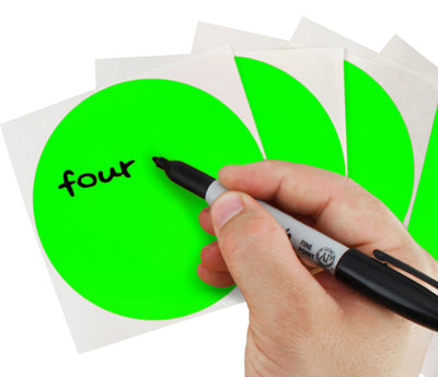 A Person's hand writing the word four on a sticker with a felt tip marker