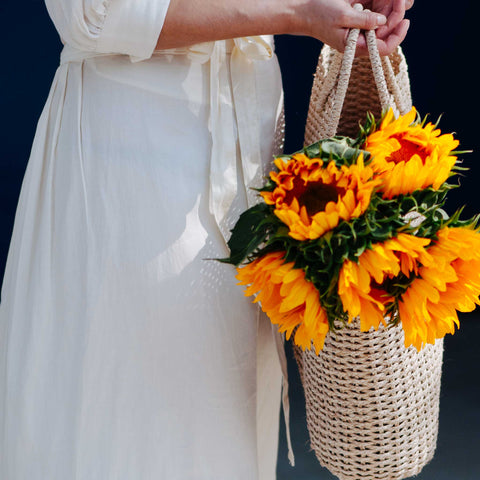 Woman holding Brigette Basket Bag with flowers inside