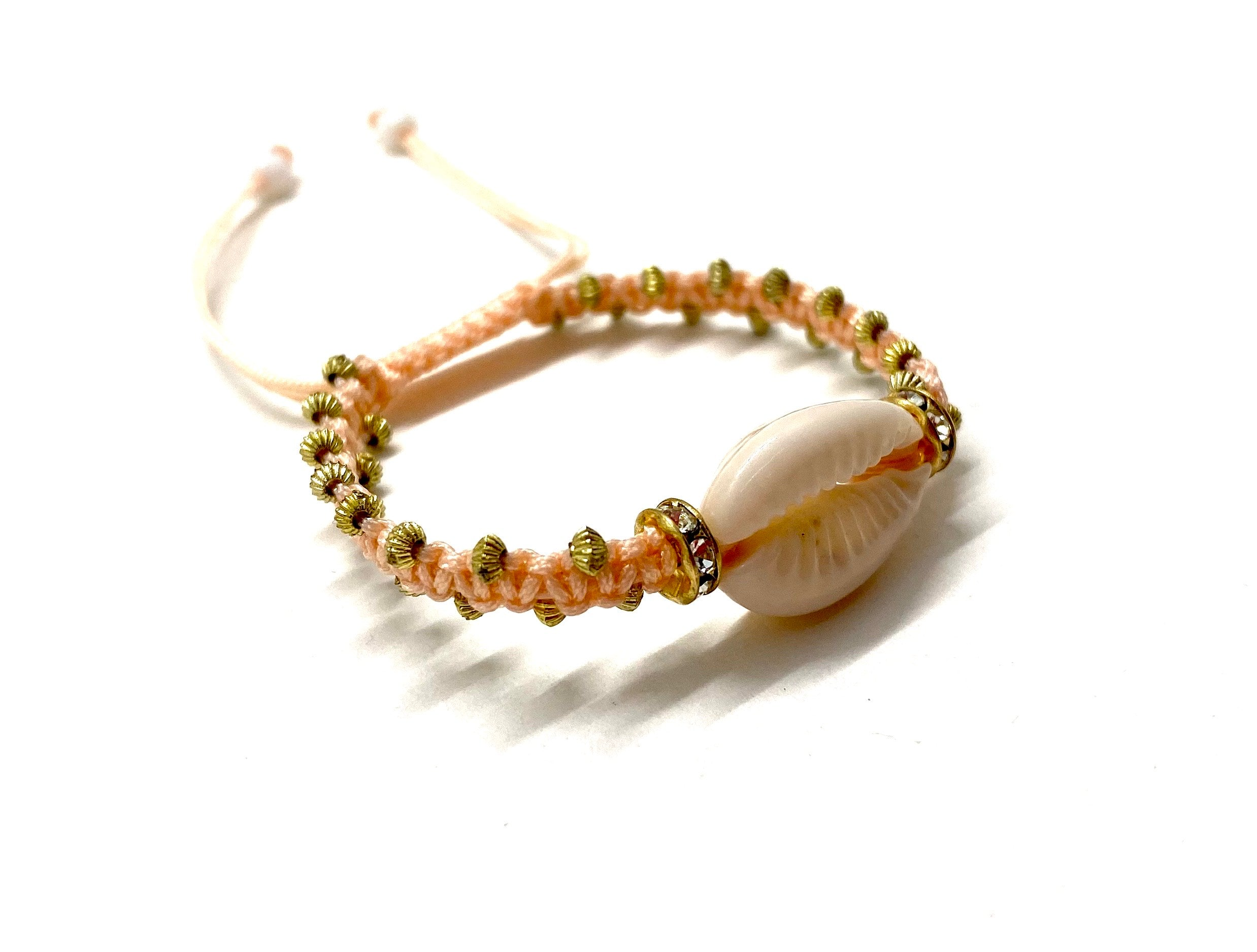 Natural shell bracelet pastel peach cord, gold toupee