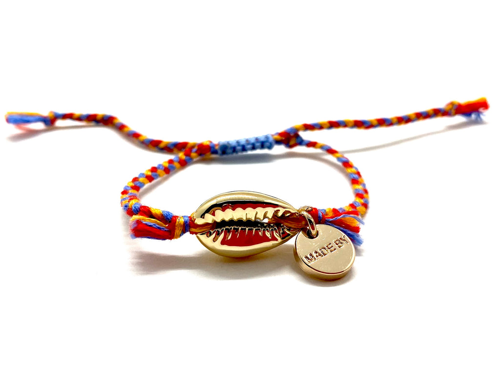 Gold shell bracelet, 'cotton perlé' with mustard, blue, and red braided cord