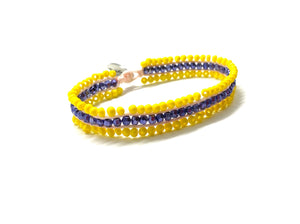 Beaded bracelet, yellow and purple seed beads and yellow cord.