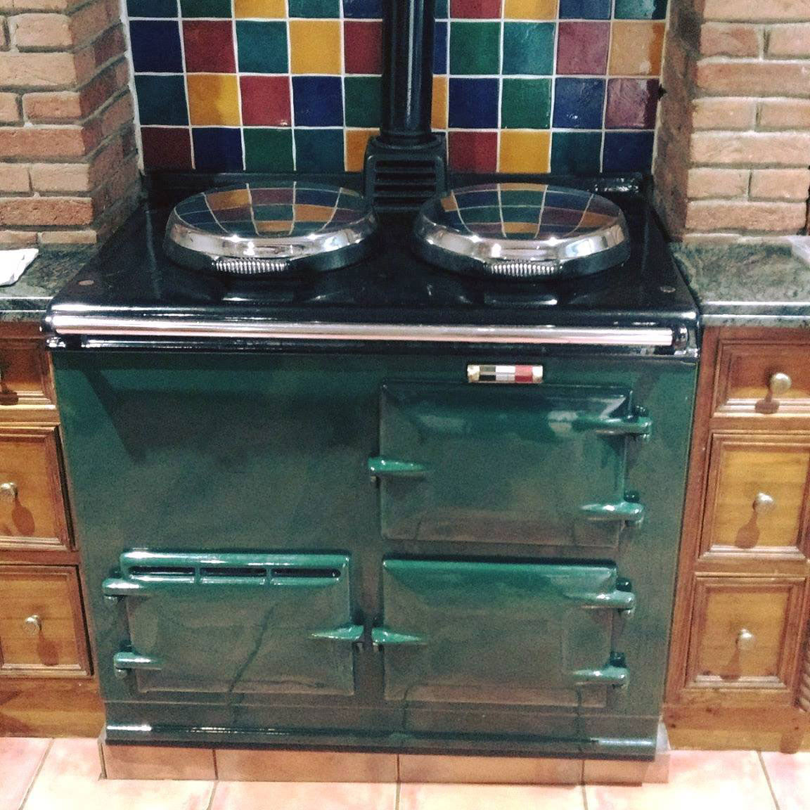 Green oil Aga range cooker with wood kitchen