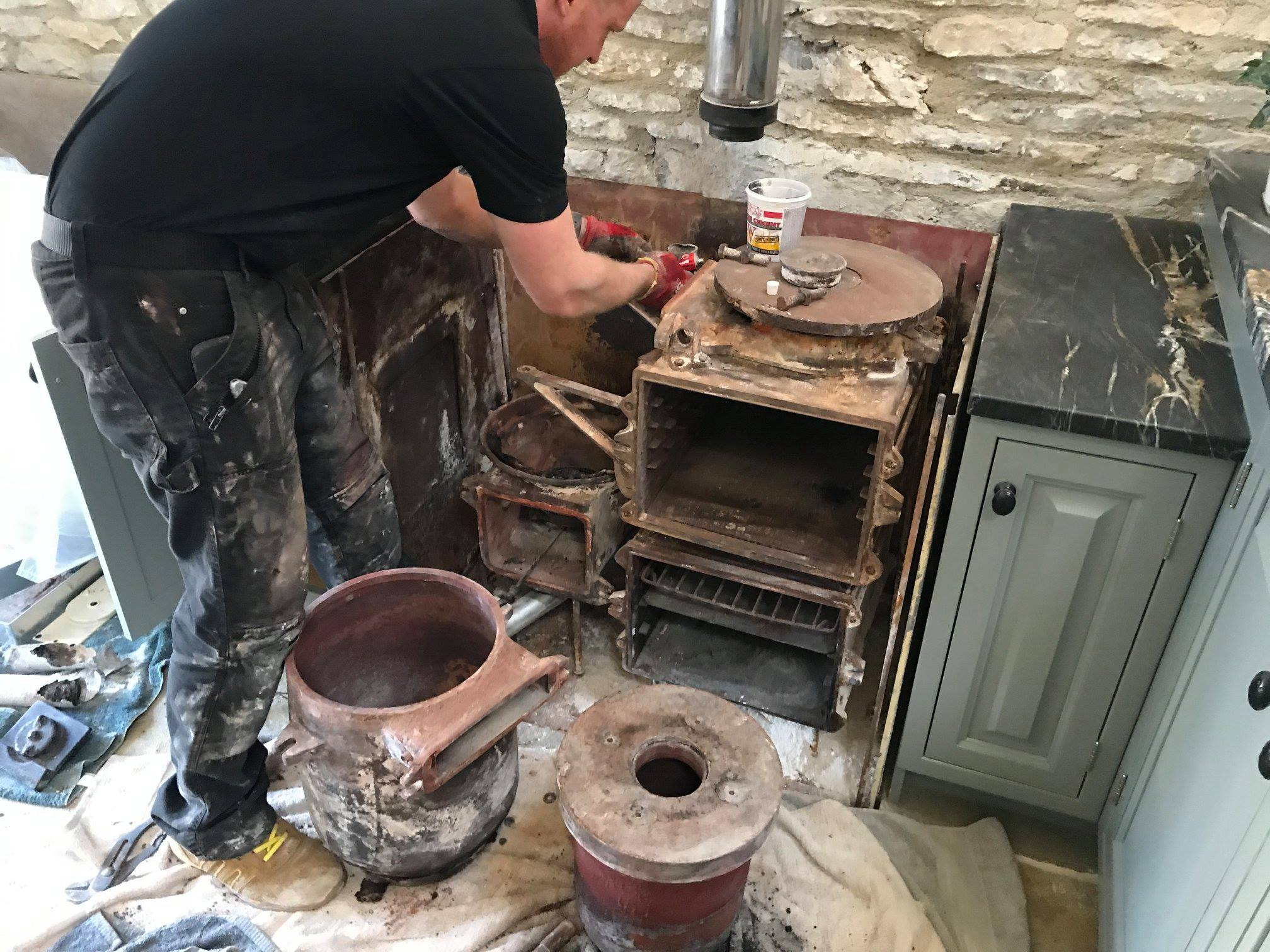 Dismantled Aga range cooker with engineer working on it