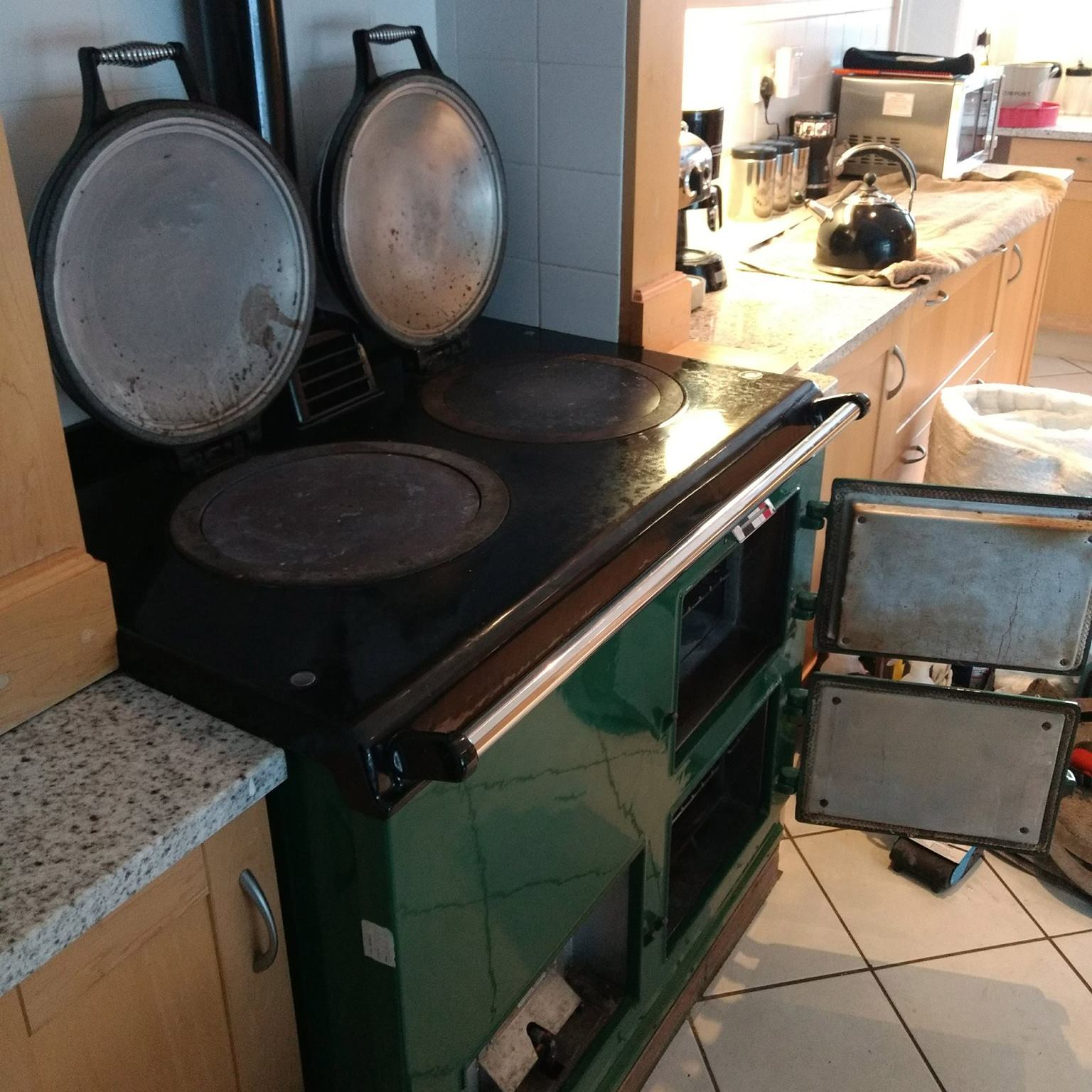 Green Aga range cooker with lids up