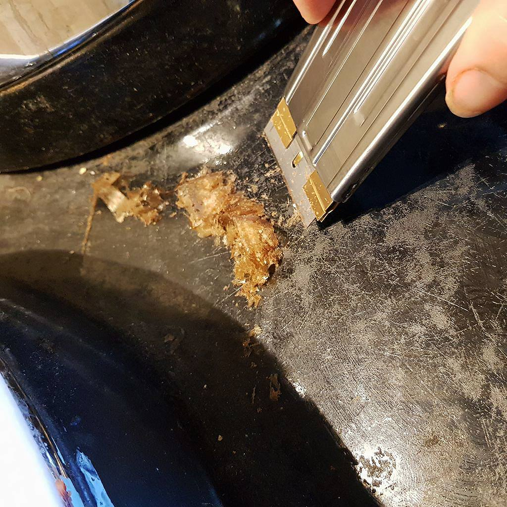 Scraping the enamel top of an Aga range cooker