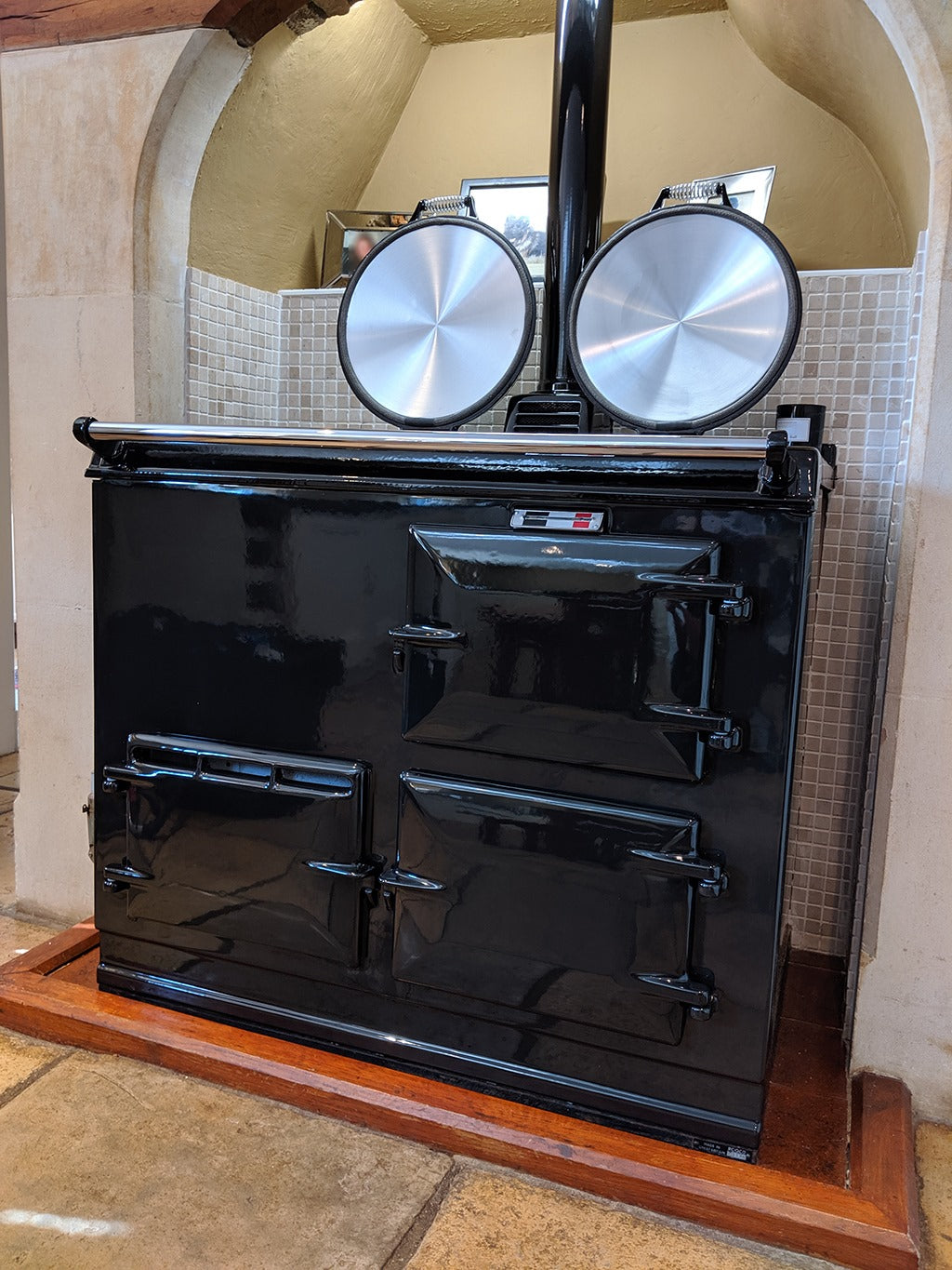 Black re-enamelled Aga range cooker with lids up