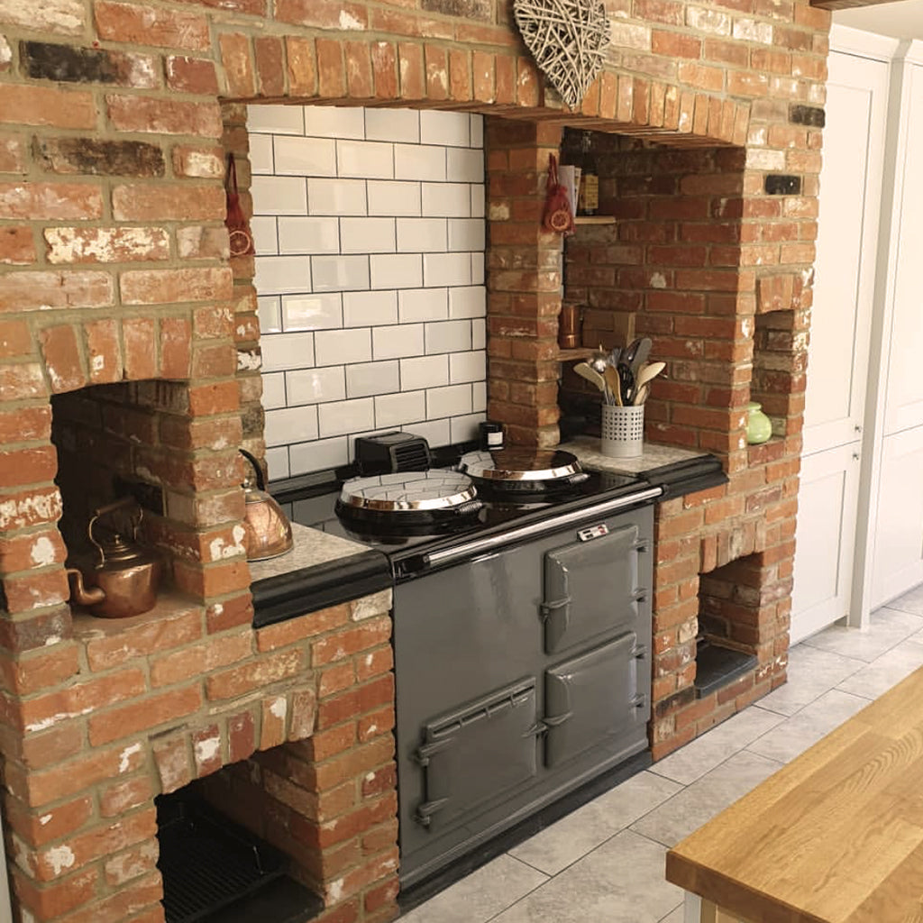 A brick fir surround inglenook refurbished grey aga range cooker