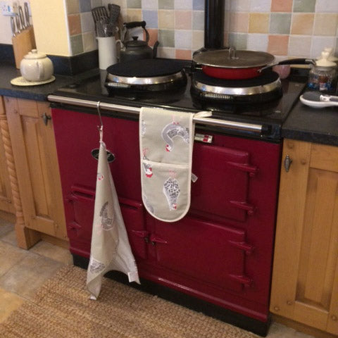 Red cooker with chicken oven gloves and tea towel