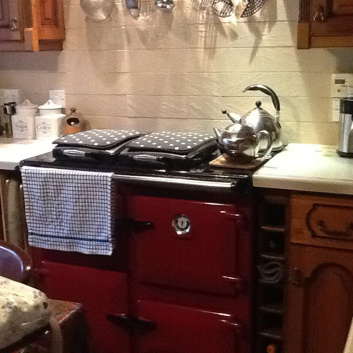 Red Rayburn range cooker with towel and chefs pads